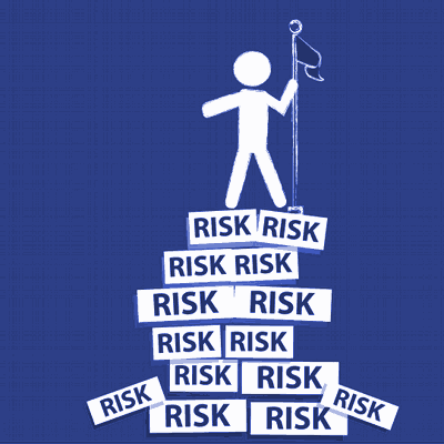 A cartoon man stands triumphantly on top of a pile of signs which all say 'Risk'.